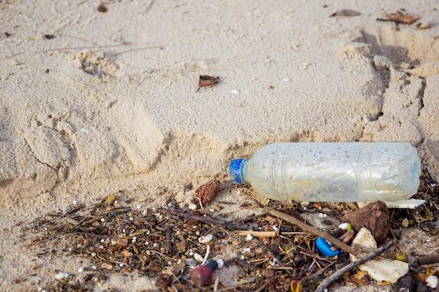 Praia suja totalmente com lixo plástico e ambiente poluído.