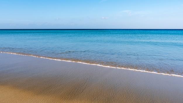 Praia tropical com céu azul e onda batendo na costa arenosa