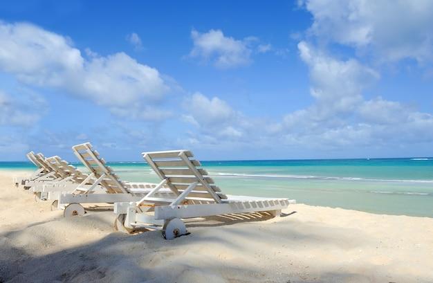 Praia tropical com espreguiçadeira de frente para o mar azul