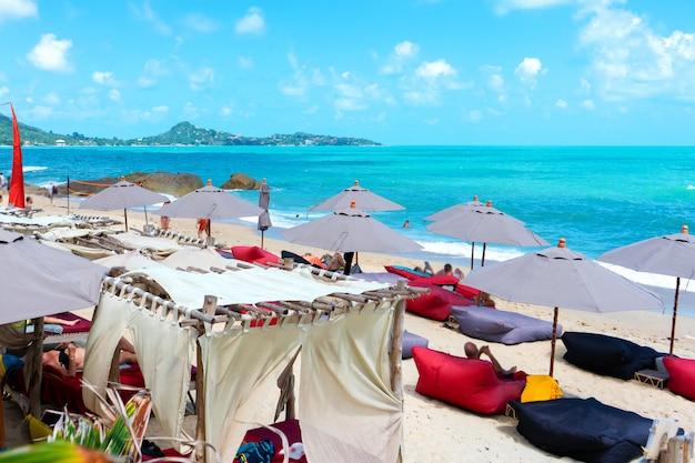 Praia tropical com galhos de palmeiras e espreguiçadeiras confortáveis.
