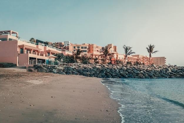 Praia tropical com hotéis em fujairah. emirados árabes unidos