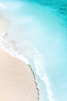 Praia tropical com uma visão panorâmica das ondas quebrando na praia tropical de areia dourada. as ondas do mar circulam suavemente ao longo da bela praia de areia.