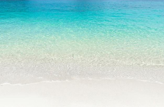 Praia tropical do verão e fundo azul transparente da água do mar.