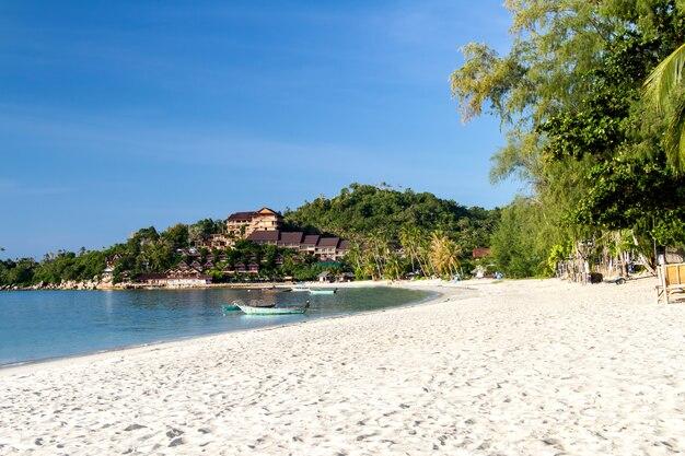 Praia tropical e areia no pôr do sol