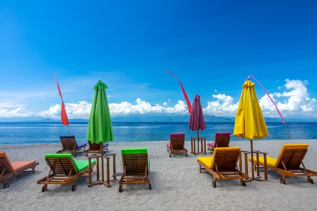 Praia tropical e céu azul com nuvens. espreguiçadeiras vazias e guarda-sóis fechados