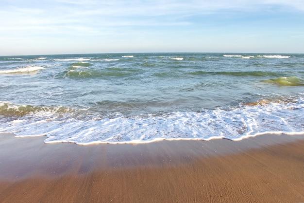 Praia tropical e oceano ondas na praia de areia macia.
