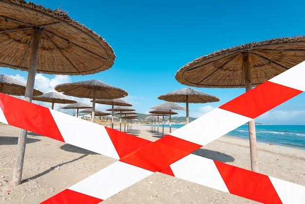 Praia vazia com fita isolante, praia de verão fechada, imagem conceitual sobre bloqueio e pandemia no mundo