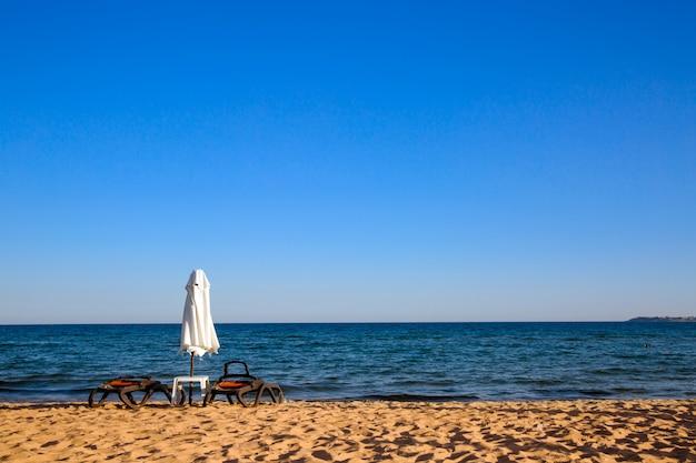 Praia vazia com guarda-chuva sunbed e fechado.