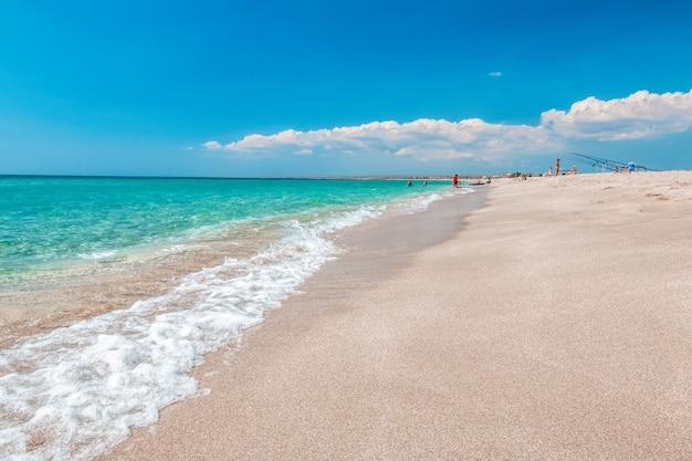 Praia vazia e deserta com areia branca e mar cristalino.