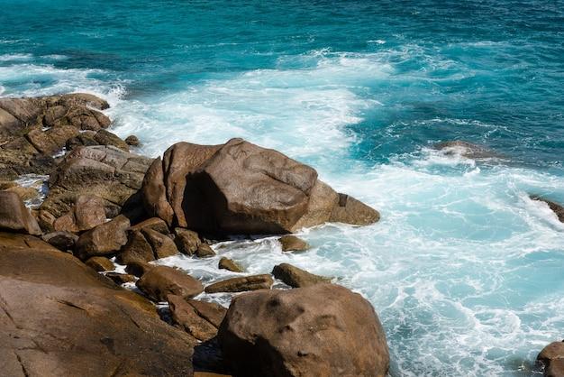 Praia ventosa nas seychelles com pedras e ondas