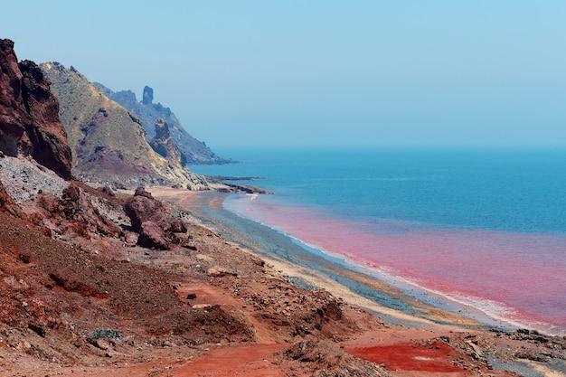 Praia vermelha na ilha iraniana de hormuz, província de hormozgan, sul do irã, o solo colorido é a atração principal.