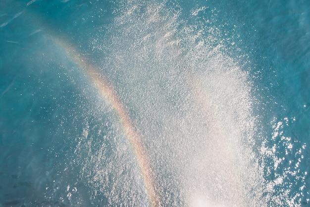 Praia viagens e meio ambiente conceito arco-íris no fundo do oceano azul oceano água superfície textura vi ...