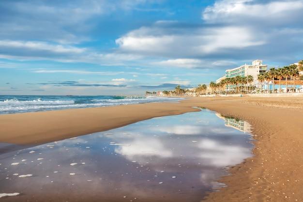 Praia villajoyosa com reflexos das nuvens em uma piscina de água na areia, alicante, espanha.