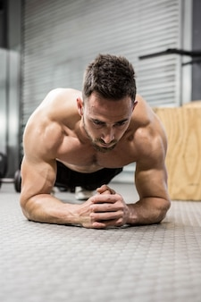 Prancha de homem sem camisa no ginásio crossfit