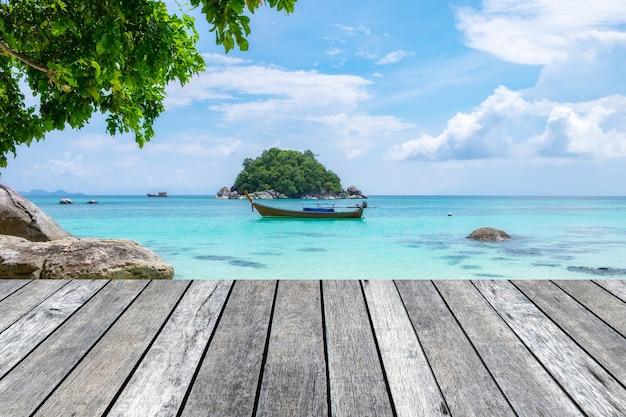 Prancha de madeira cinza no mar de cristal com barco de cauda longa