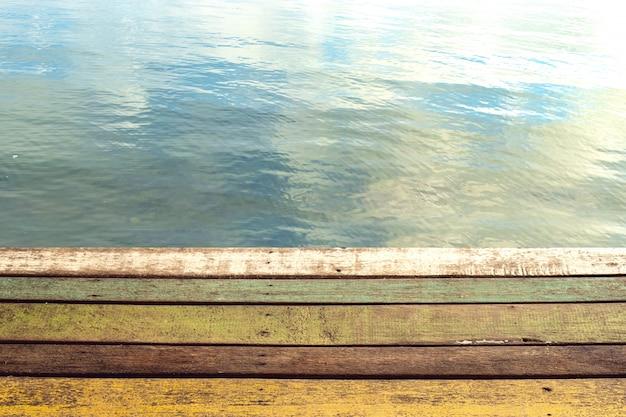Prancha de madeira de cor do cais com água de fundo do lago