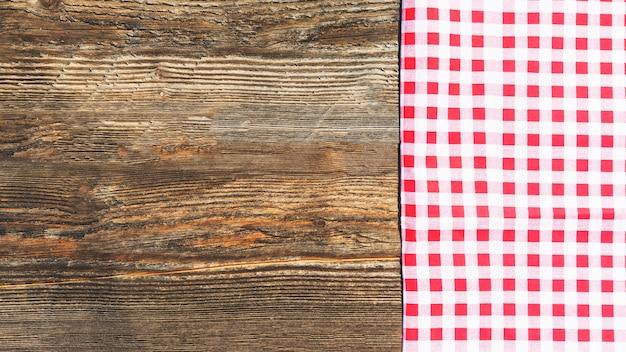 Prancha de madeira texturizada e toalha de mesa quadriculada