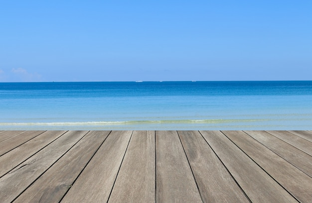 Prancha de madeira vintage com fundo azul brilhante do mar e céu