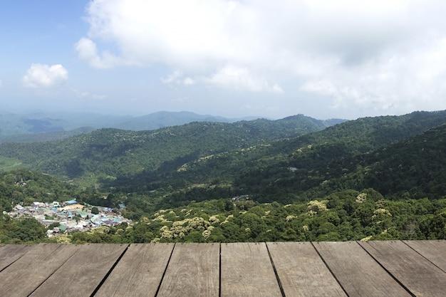 Prancha de madeira vintage, piso, mesa em perspectiva da montanha com céu azul de fundo para exibição