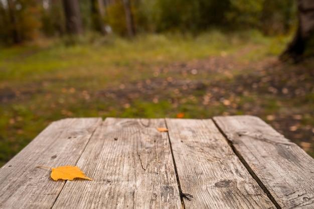 Prancha de mesa vazia de madeira no outono desfocar o fundo, espaço para texto. foto de alta qualidade