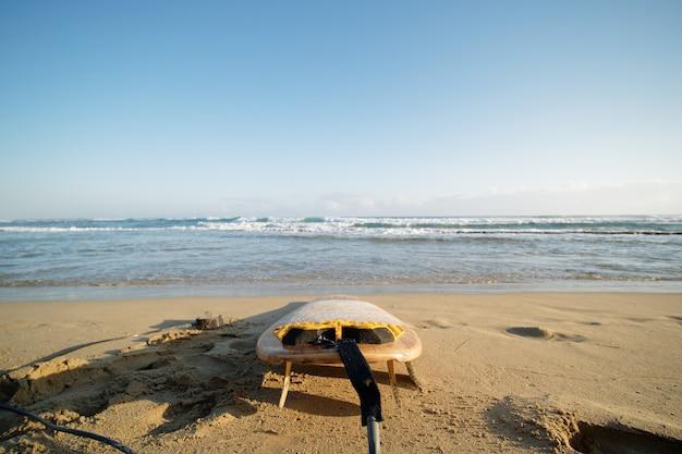 Prancha de surf na praia do oceano atlântico na hora da manhã. foco seletivo.