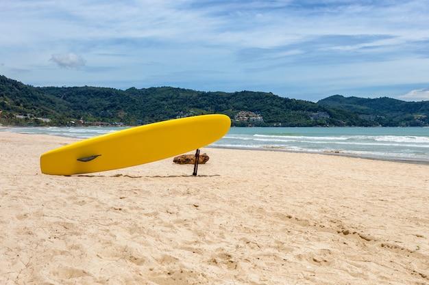 Prancha de surfe amarela na praia com montanha na praia de patong