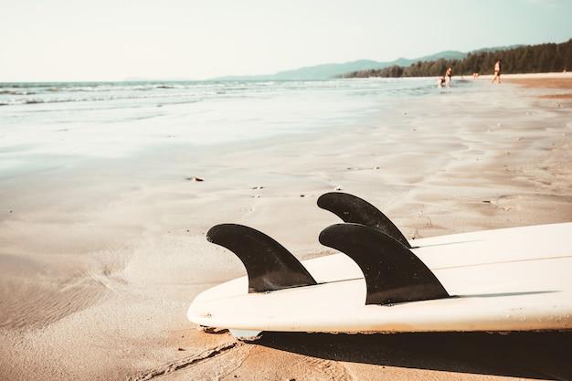 Prancha na praia tropical da areia com fundo calmo do mar e do céu do seascape.