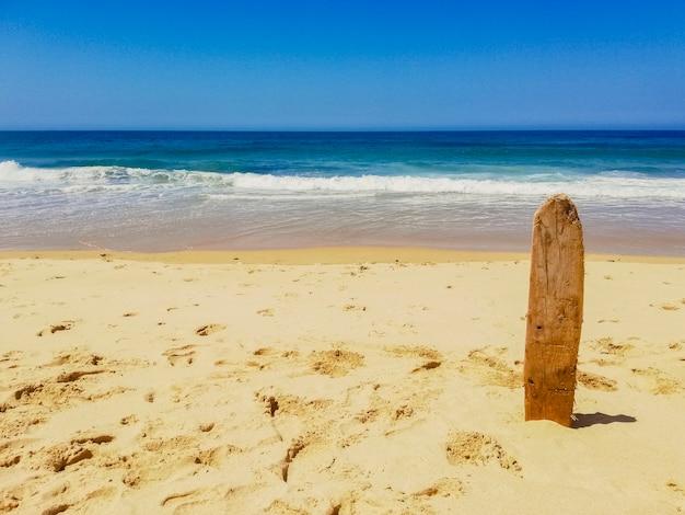 Prancha velha colada na areia de uma praia.