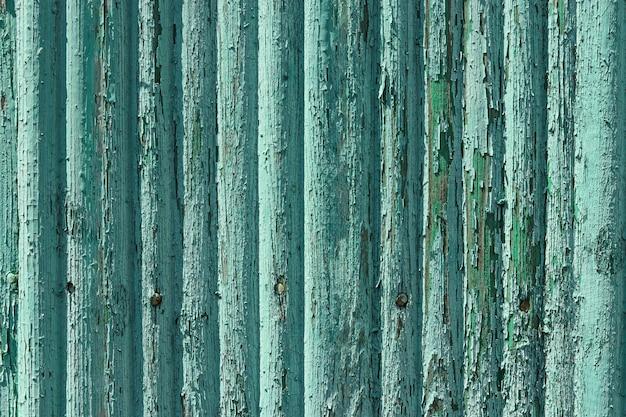Pranchas de madeira gasto velhas com pintura de cor verde rachada, fundo do país rural