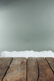 Pranchas de madeira velhas com neve em fundo cinza