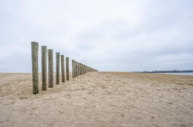 Pranchas de madeira verticais de um deck inacabado na praia sob um céu nublado