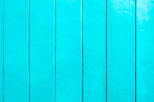 Pranchas de madeira verticais fecham o fundo. a parede é pintada de cor azul claro. pinte em placas.