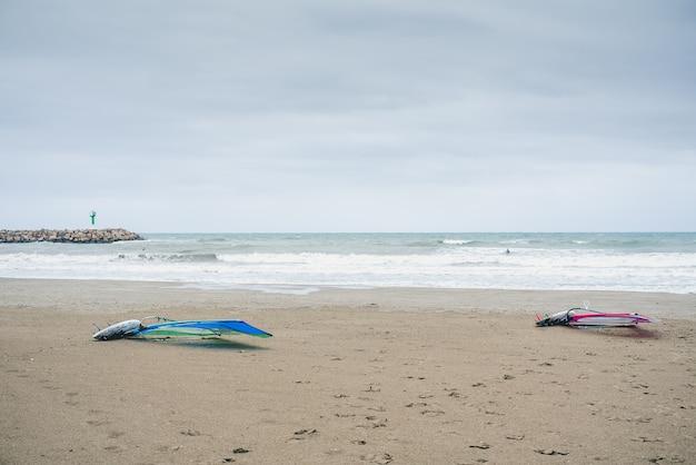 Pranchas de windsurf na areia de uma praia espanhola, enquanto os surfistas esperam pela onda certa.