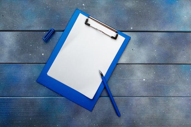 Prancheta azul na mesa de escritório, vista superior, plana leigos