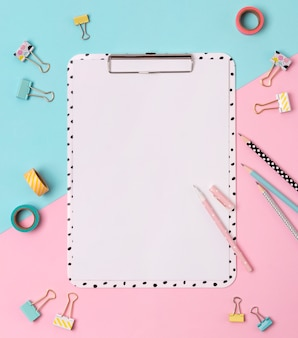 Prancheta, caneta, fichário, lápis e fita adesiva na mesa criativa de rosa e azul.
