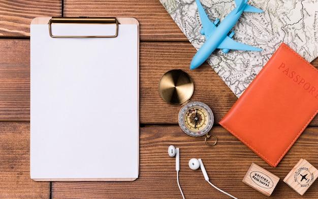 Prancheta com bússola e passaporte em cima da mesa