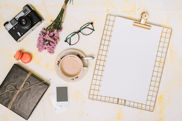 Prancheta com café, câmera e buquê de flores na mesa