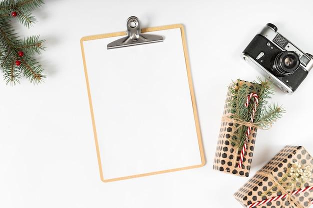 Prancheta com caixas de presente e câmera na mesa