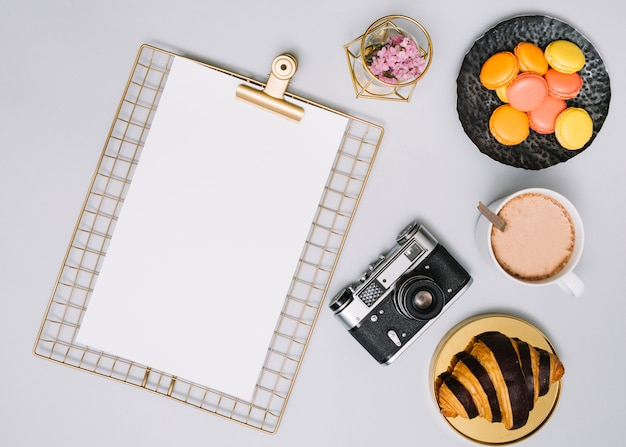 Prancheta com câmera, biscoitos e croissant