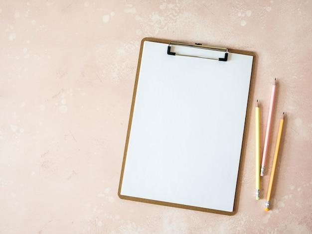 Prancheta com folha de papel branco e lápis de grafite multicolorido