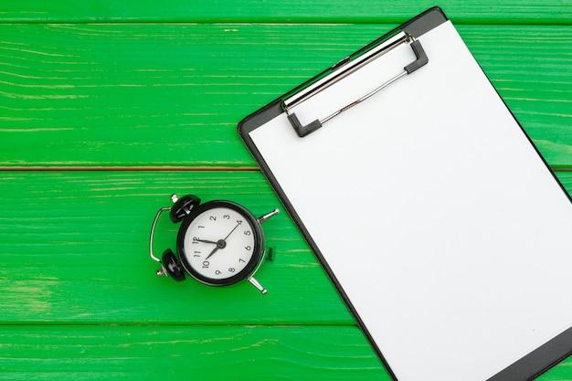 Prancheta com folha de papel em branco branca no verde de madeira, copie o espaço