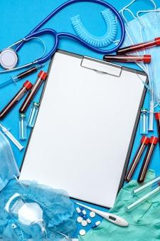 Prancheta com folha de papel em branco com ferramentas médicas em fundo azul