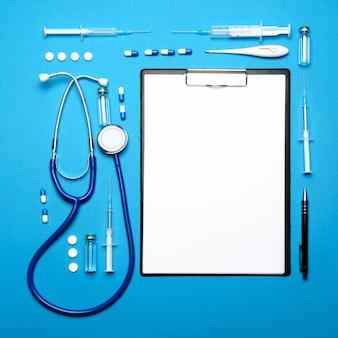 Prancheta com folha de papel em branco e suprimentos médicos sobre fundo azul.