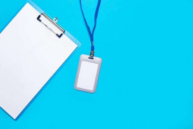 Prancheta com folha em branco e crachá de plástico com cordão azul na superfície azul claro