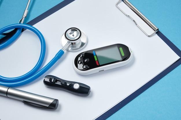 Prancheta com folhas de papel em branco brancas, estetoscópio, medidor de glicose, lanceta e caneta de seringa com insulina em fundo azul, conceito de dia daibet, diagnóstico de diabetes