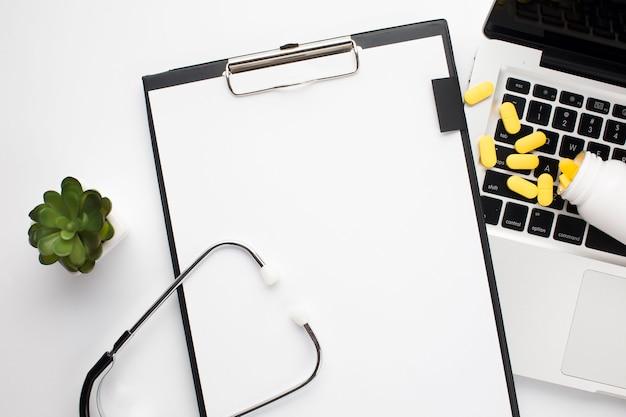 Prancheta com papel branco perto de pílulas derramando no laptop e estetoscópio sobre a mesa