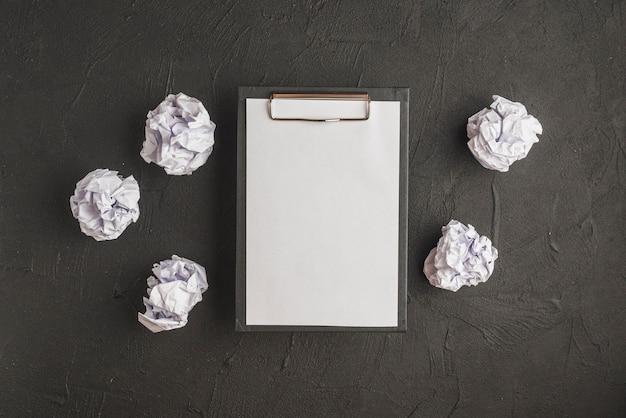 Prancheta com papel cercado por papéis amassados no pano de fundo preto