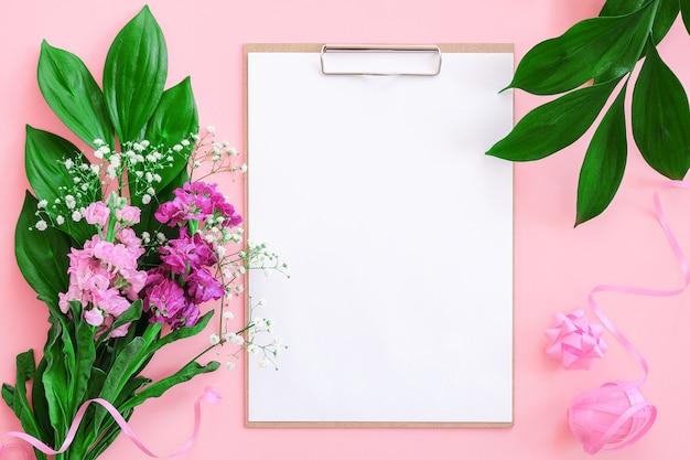 Prancheta com papel em branco branco, caneta e buquê de flores na parede rosa. espaço de trabalho feminino conceito