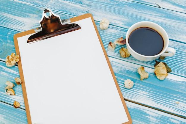 Prancheta com papel em branco branco na mesa de madeira azul, vista de cima