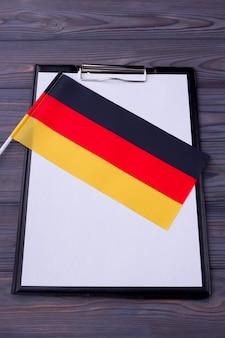 Prancheta com papel em branco para espaço de cópia e bandeira da alemanha
